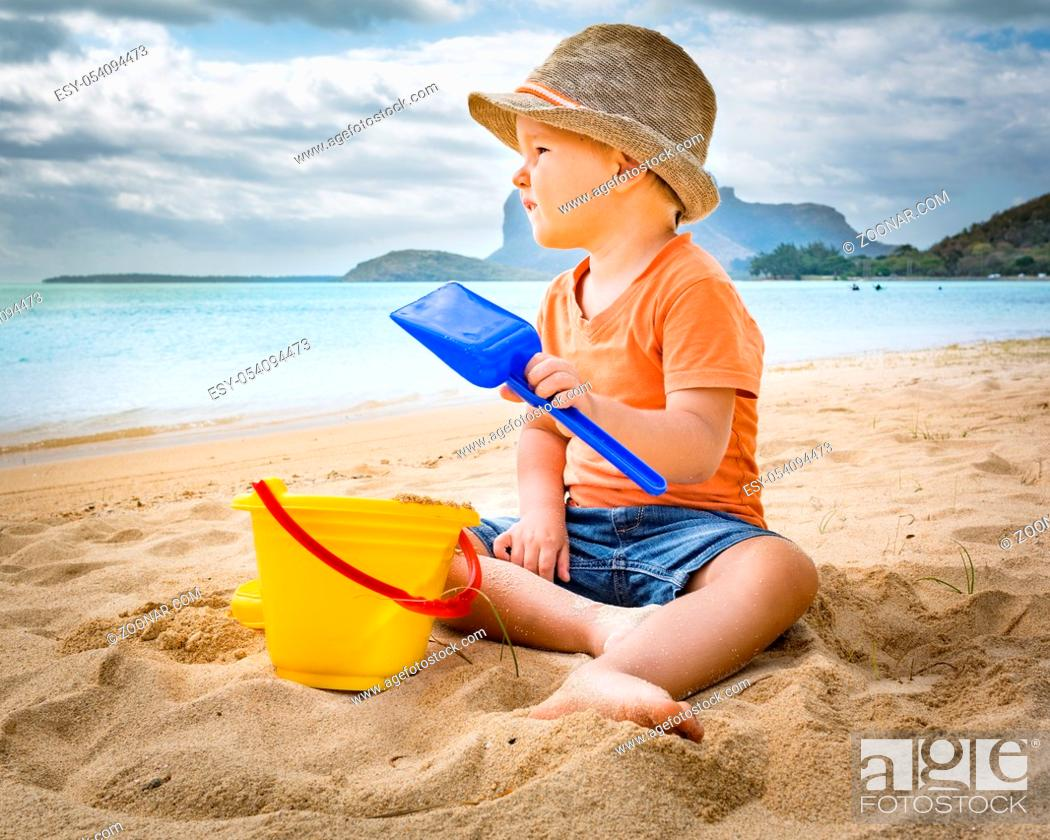 Stock Photo: Cute boy on the tropical beach playing toys.