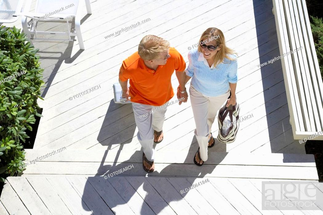 Stock Photo: Couple with luggage walking up steps high angle view.