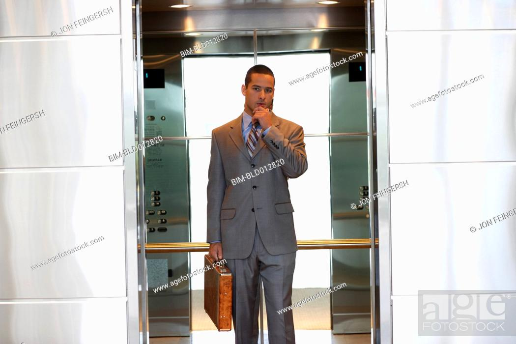 Stock Photo: Young businessman inside elevator.