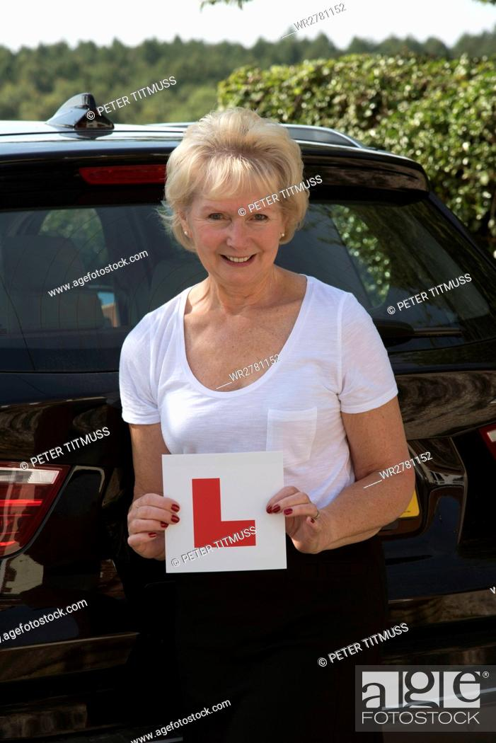 Stock Photo: Elderly woman driver with an self adhesive L plate.