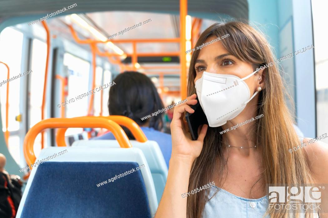 Stock Photo: Woman wearing face mask talking on the phone onboard train. High quality photo.