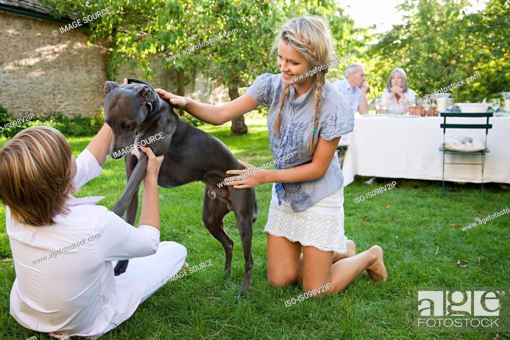 Stock Photo: Brother and sister playing with pet dog.