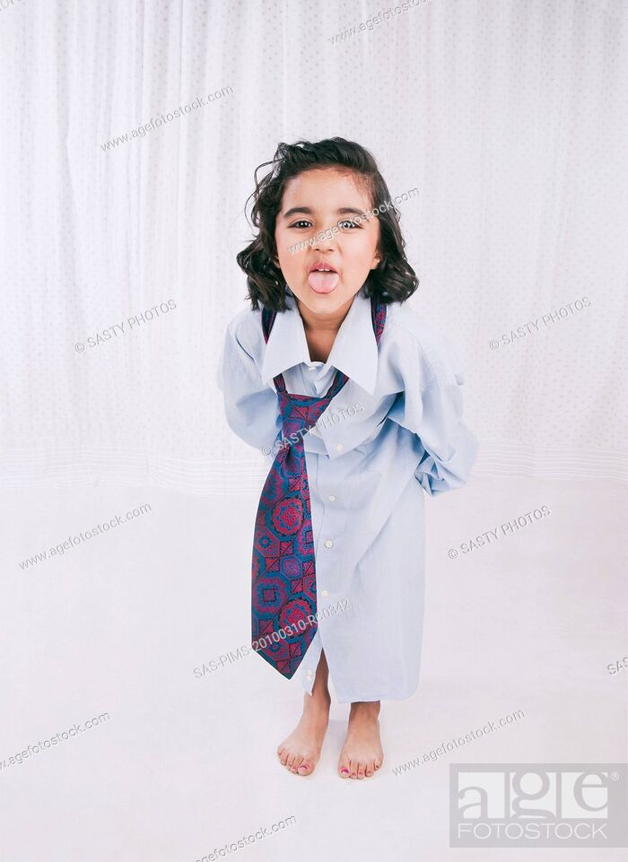 Stock Photo: Portrait of a girl wearing oversize shirt with tie and sticking her tongue out.