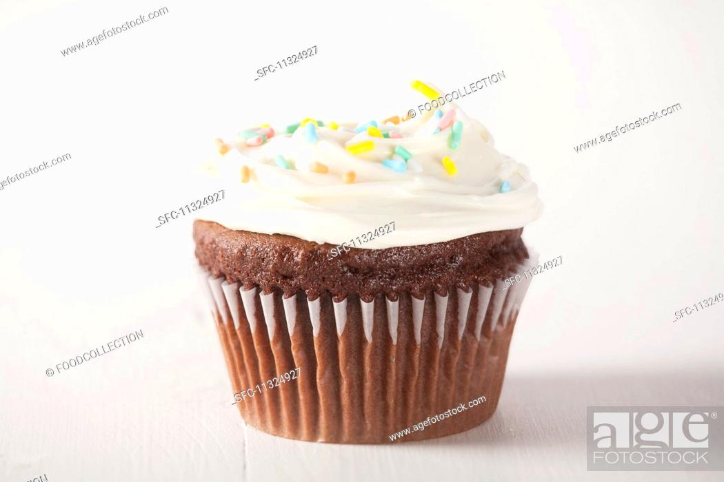 Imagen: A chocolate cupcake with white frosting and sugar sprinkles.