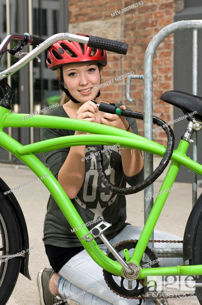 Photo de stock: Portrait of teenage girl locking bicycle, smiling.
