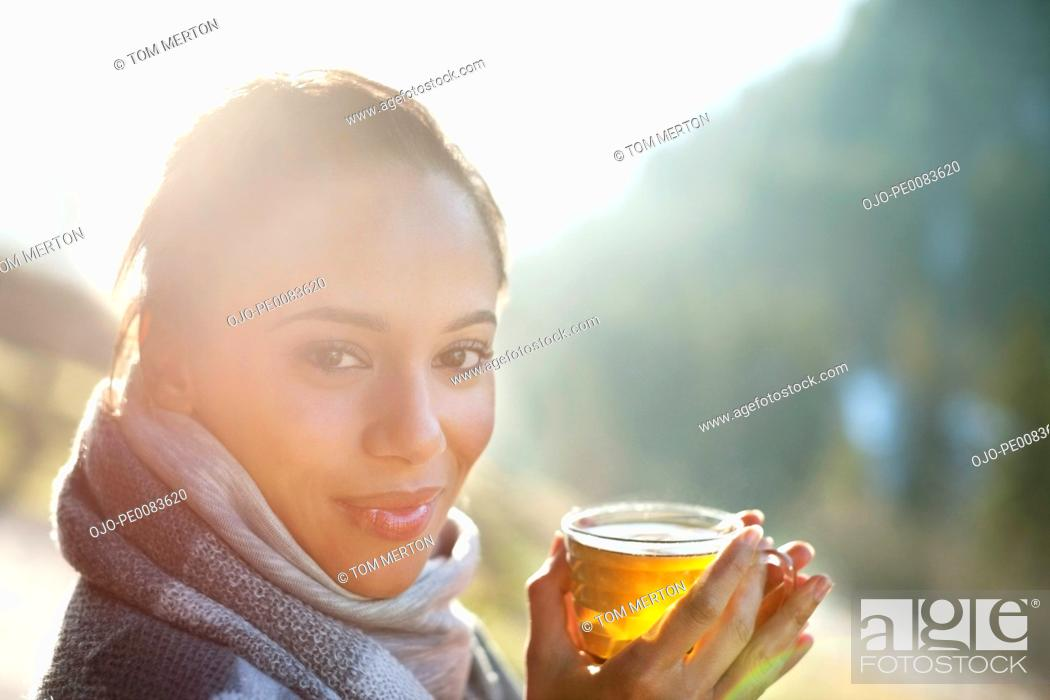 Stock Photo: Portrait of smiling woman in scarf drinking cider.