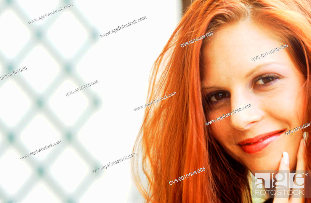 Stock Photo: Close-up of a woman with a hand on her chin.
