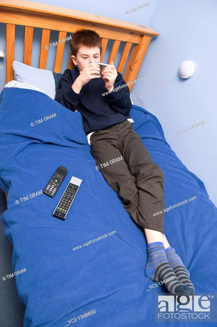 Stock Photo: A picture of an eleven year old boy playing with his ipod touch in his bedroom in the Uk.
