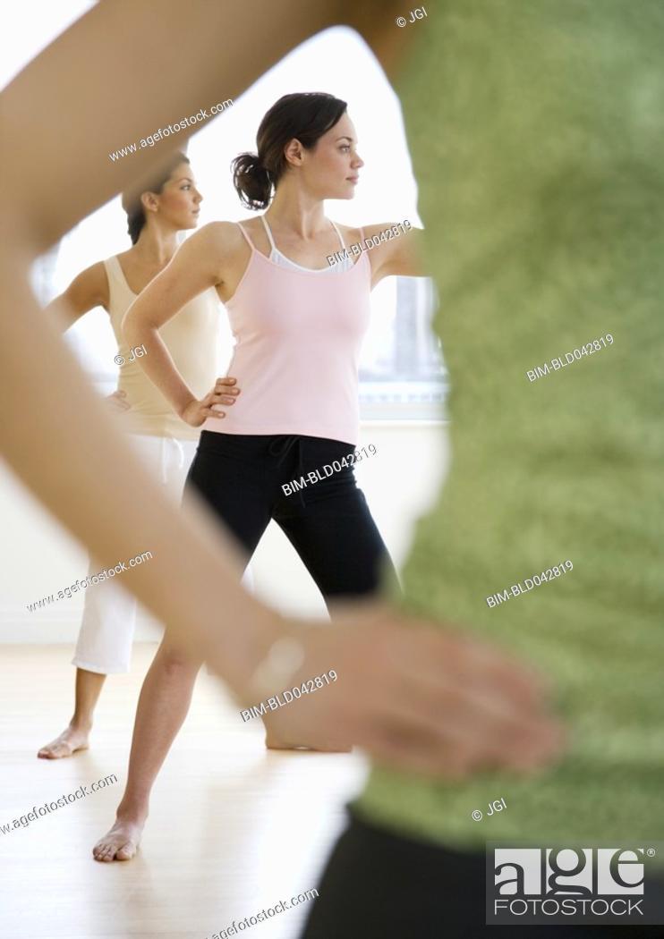 Stock Photo: Three young women in yoga class.