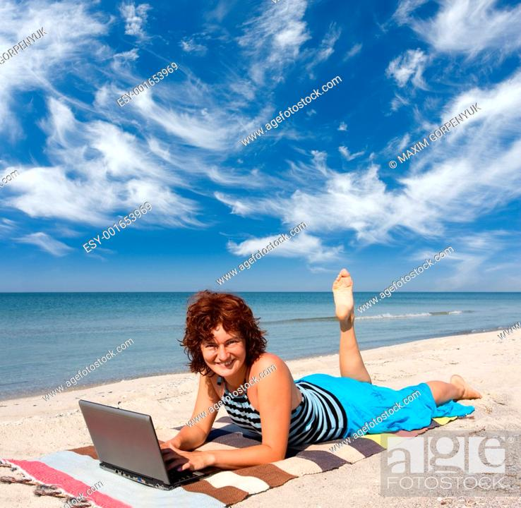Stock Photo: woman with laptop at sea beach.