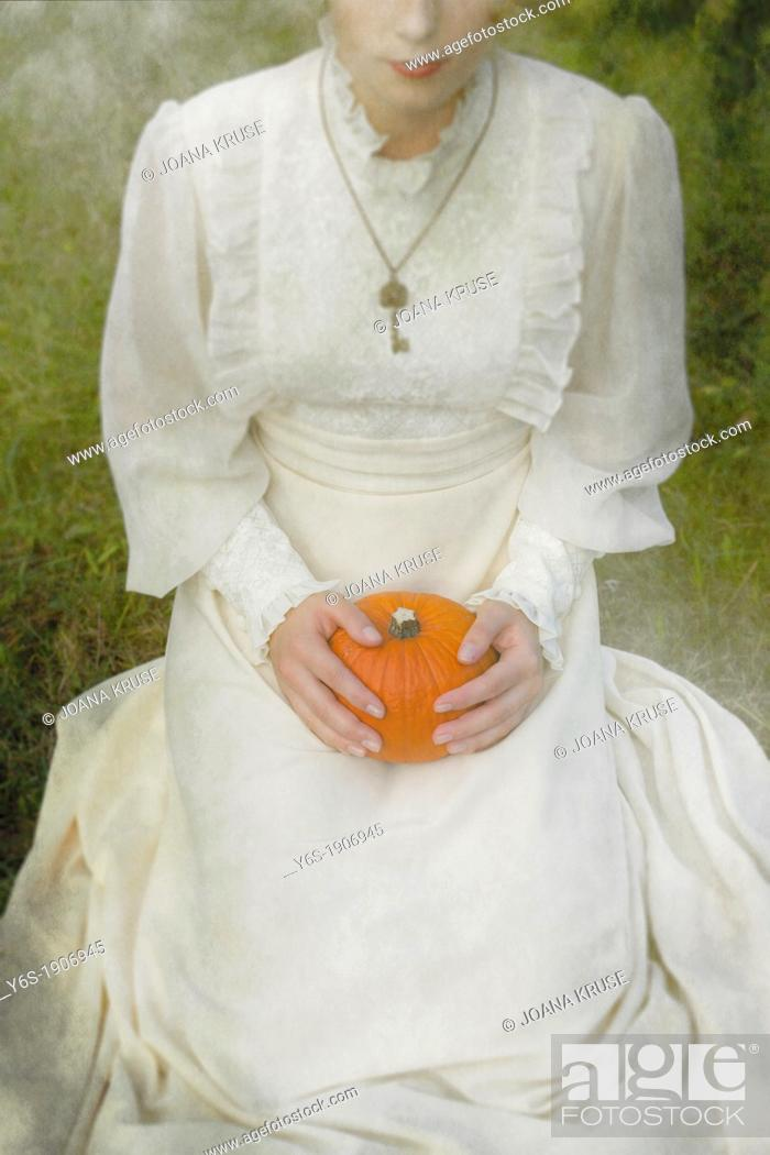 Stock Photo: a woman in a victorian dress is sitting on grass and holding a pumpkin on her lap.