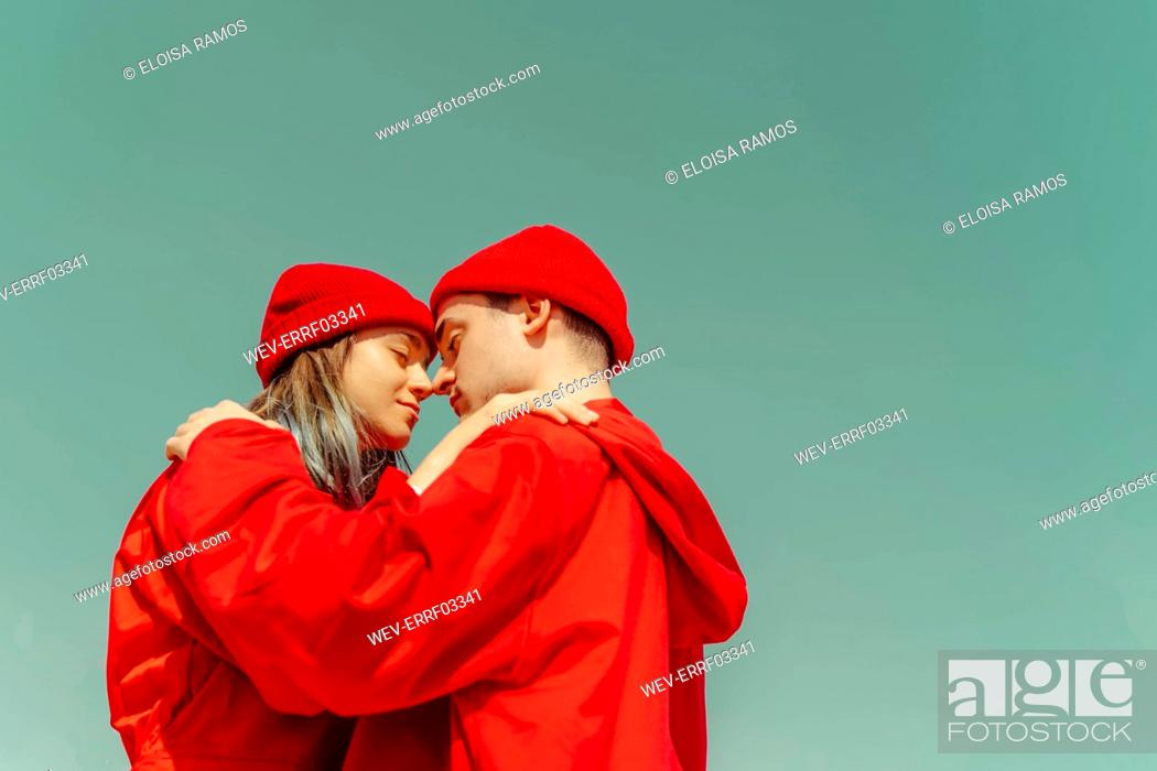 Stock Photo: Young couple wearing red overalls and hats standing head to head against sky.