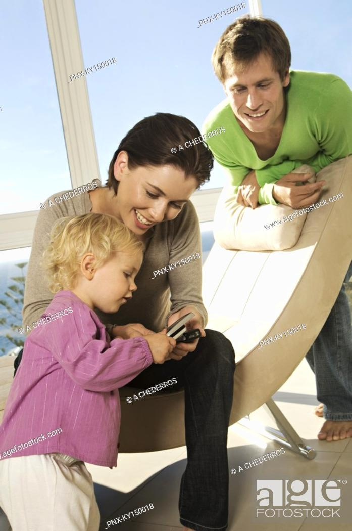 Stock Photo: Couple and little girl using mobile phone.