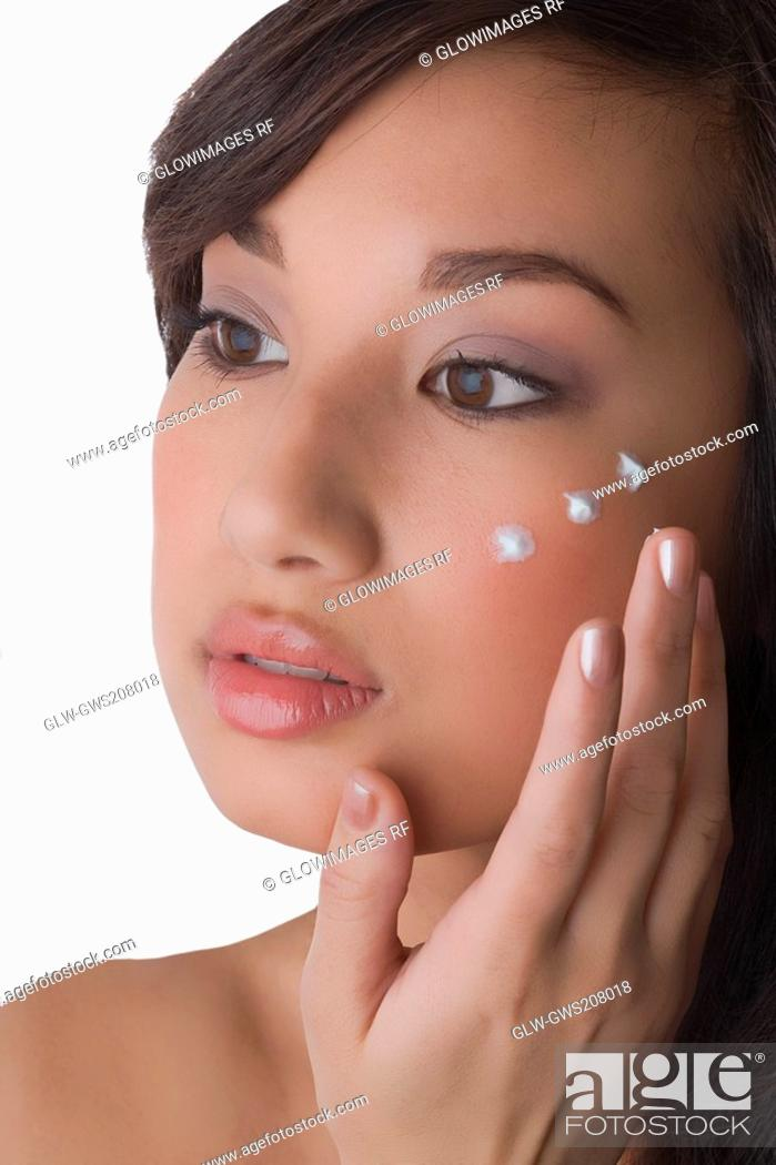Stock Photo: Close-up of a young woman applying cream on her face.