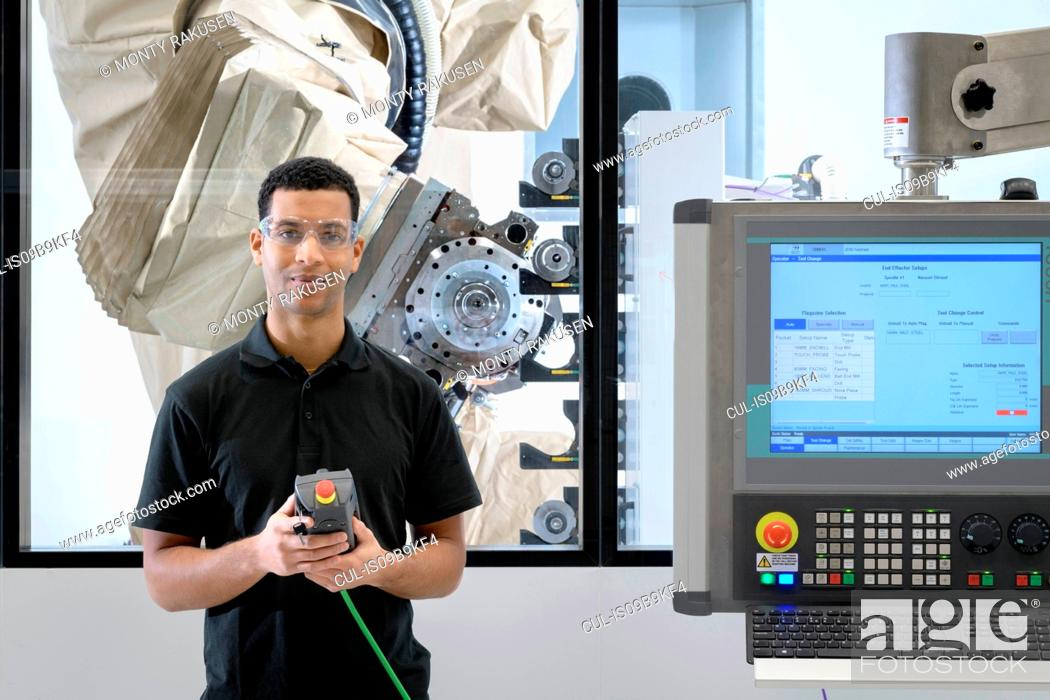 Stock Photo: Portrait of apprentice robotics engineer with robot in robotics research facility.