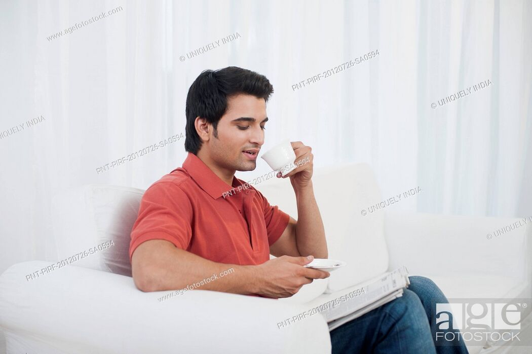 Stock Photo: Man sitting on a couch and drinking coffee.