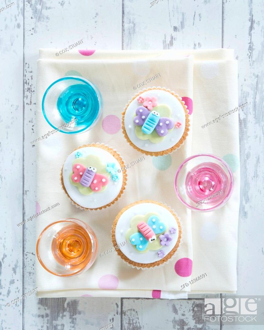 Stock Photo: Cupcakes decorated with decorative butterflies and blossoms (supervision).