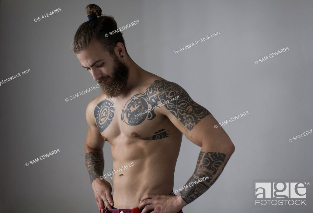 Stock Photo: Portrait bare chested man with tattoos and beard.