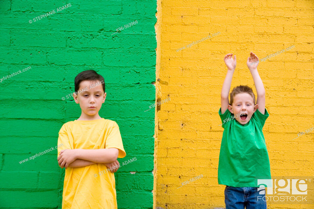 Stock Photo: Two boys against colorful yellow and green wall.