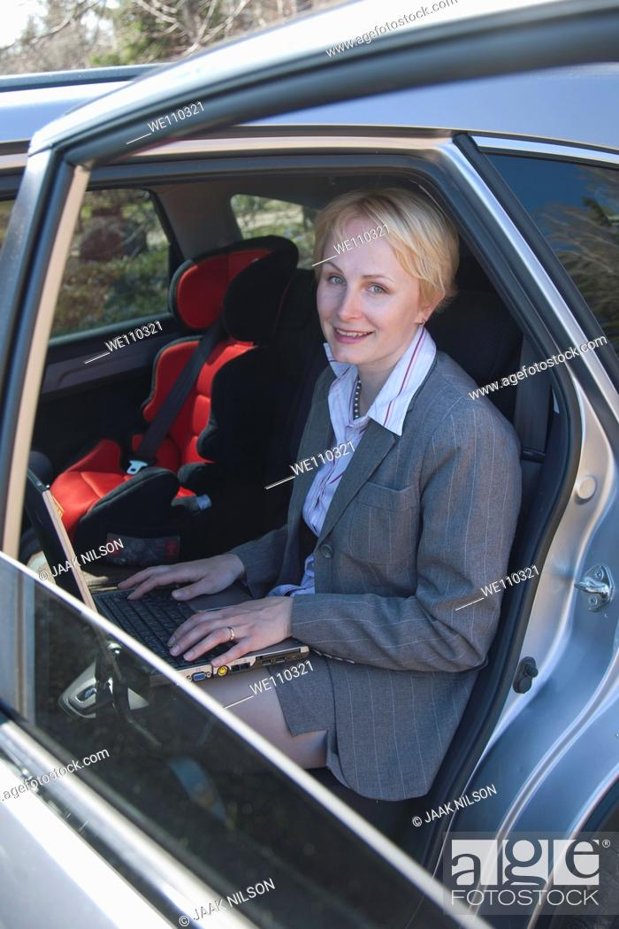 Stock Photo: Happy Smiling Businesswoman With Laptop Computer Sitting in Car.