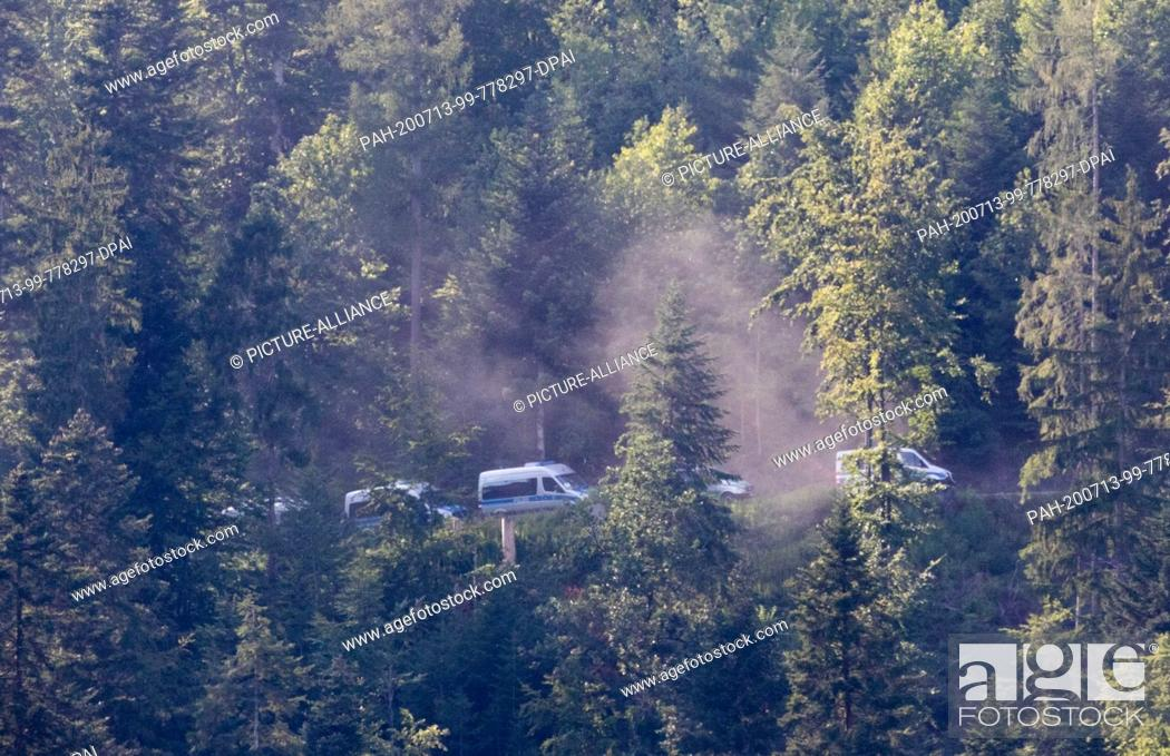 Stock Photo: 13 July 2020, Baden-Wuerttemberg, Oppenau: RECROP - Police vehicles drive through the forest near Oppenau. With a large contingent.