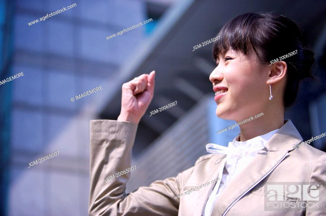 Stock Photo: Young woman smiling with fists up.