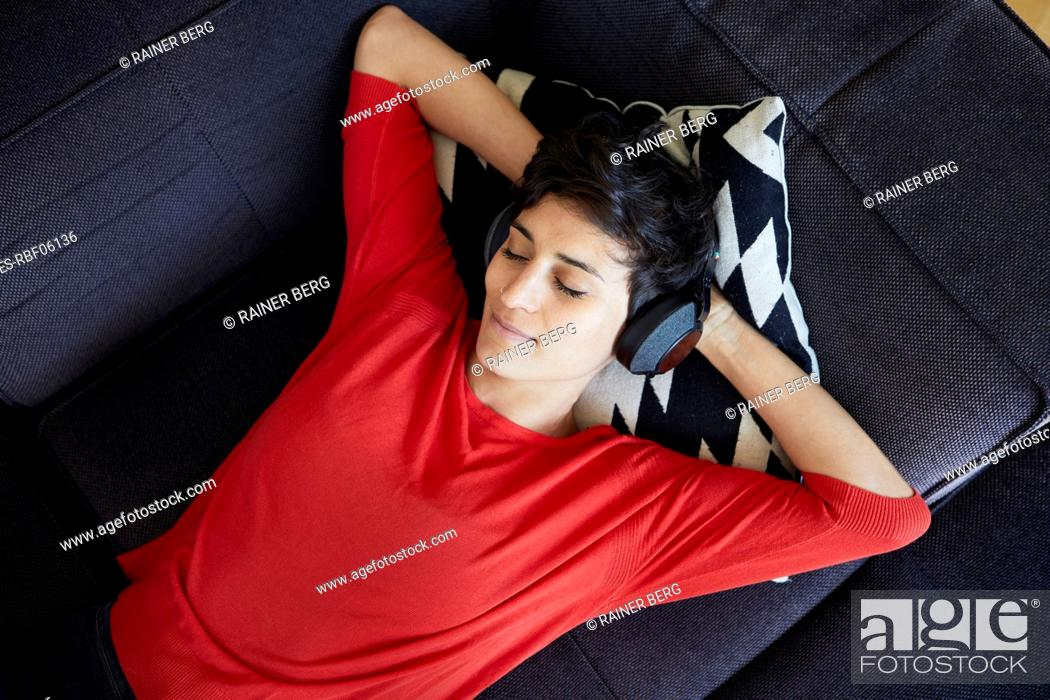 Stock Photo: Woman lying on couch at home wearing headphones.