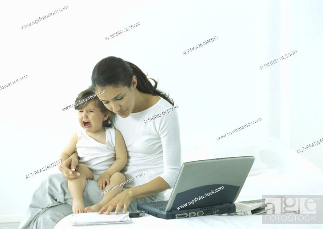 Stock Photo: Woman sitting on bed with little girl on lap crying, looking down at paper.