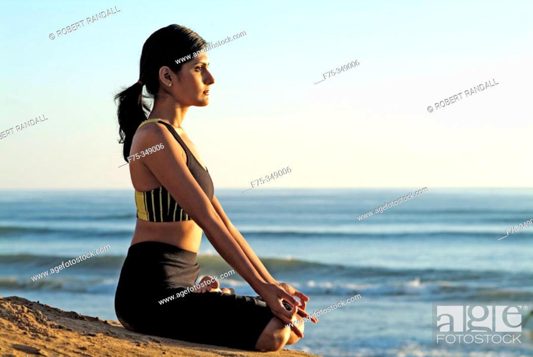 Stock Photo: Indian girl meditating on beach at sunset, Carlsbad. California, USA.
