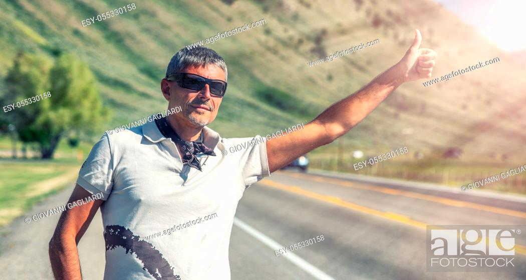 Photo de stock: Outdoor shot of travel man hitchhiking along a countryside road in casual t-shirt. Travelling, tourism and holiday concept.