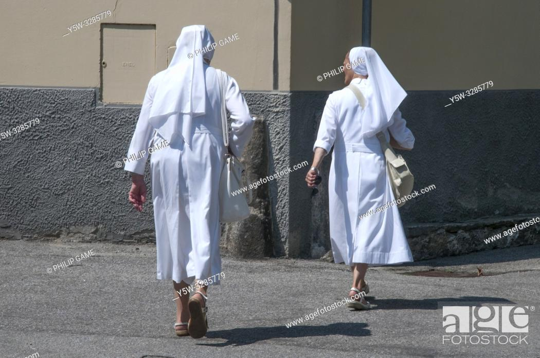Stock Photo: Two Christian nuns walking together in Domodossola, Piedmont, Italy.