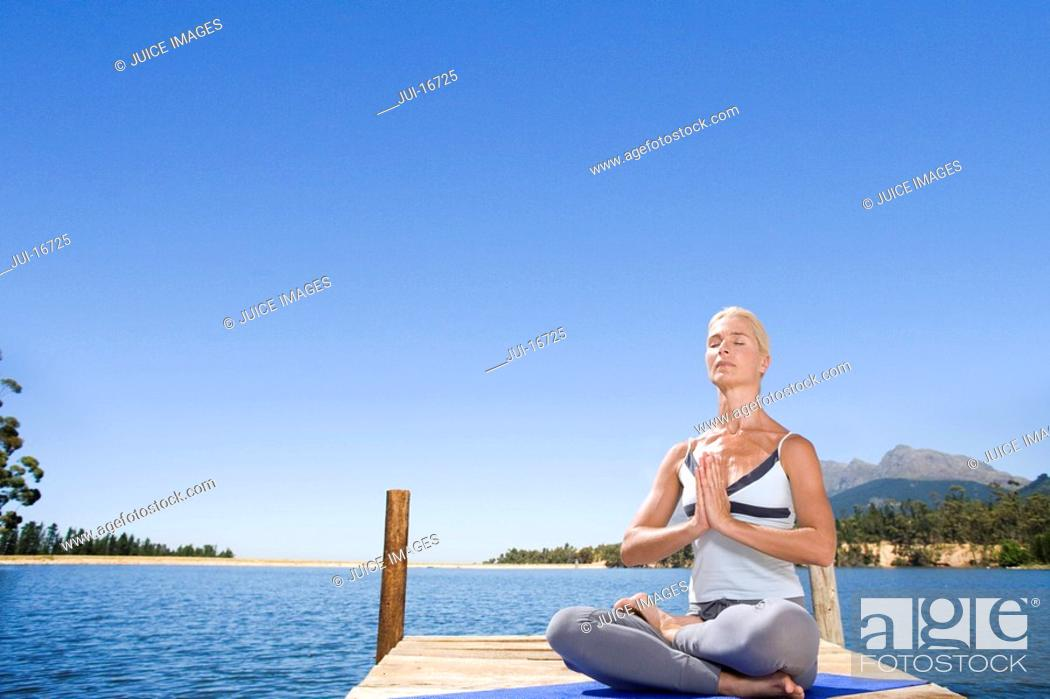 Stock Photo: Woman meditating on lake dock.