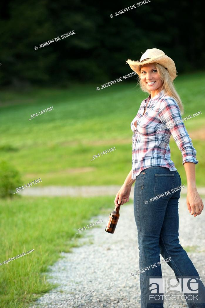 Stock Photo: Side view of a blond woman wearing blue jeans and a straw hat waliking on a country path looking back at the camera.