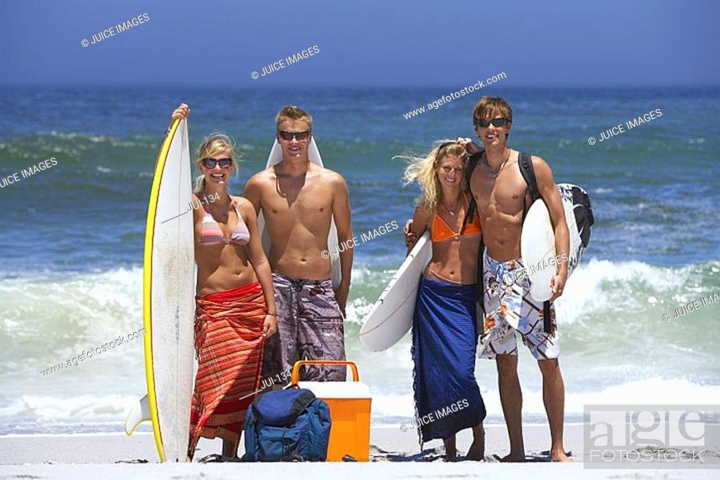 Stock Photo: Four young friends standing on sandy beach with surfboards, portrait, sea in background.