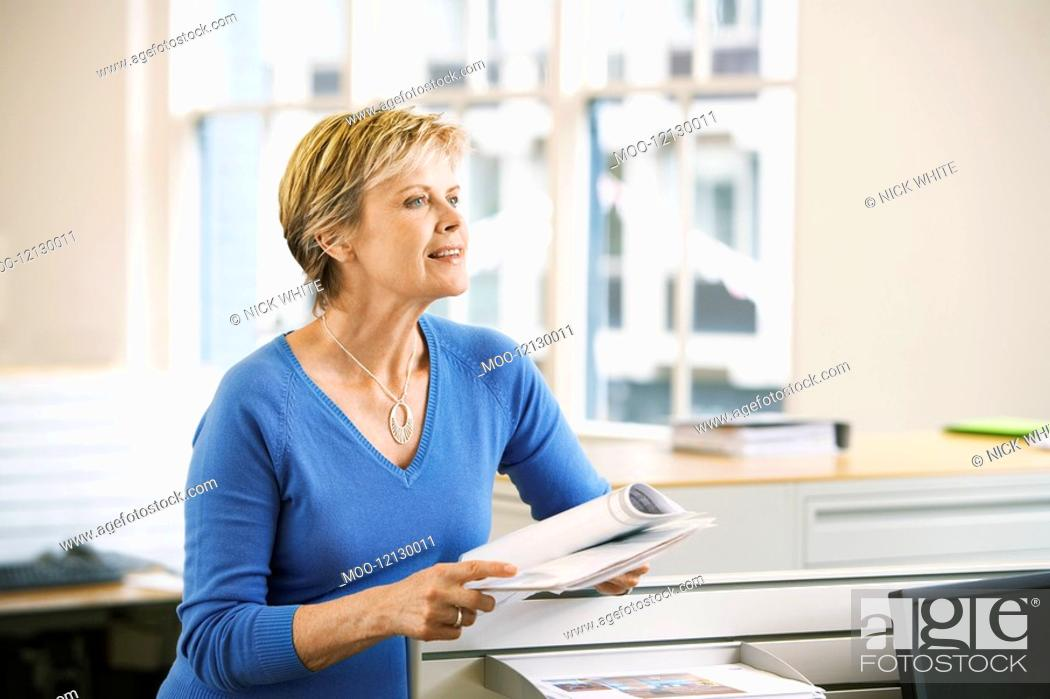 Stock Photo: Middle-aged female office worker leaning on cubicle in office holding paperwork.