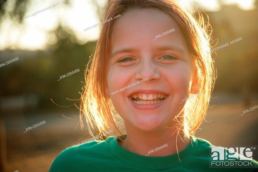 Photo de stock: Young happy girl smiling at the camera on a camping trip.