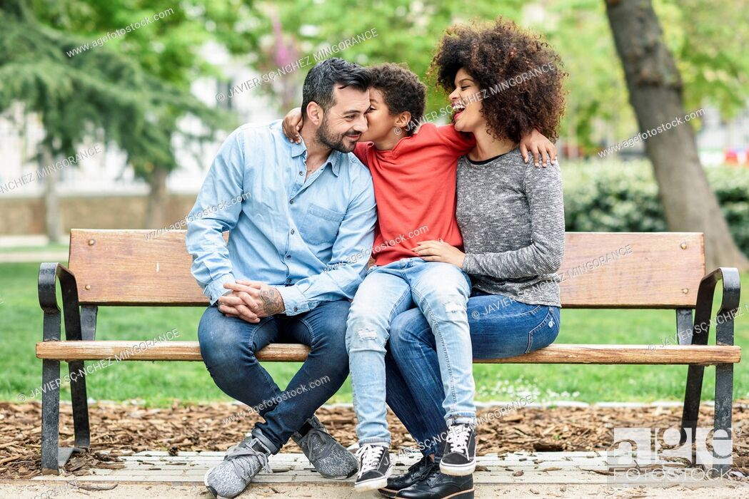 Photo de stock: Family sitting on a park bench, son kissing father.