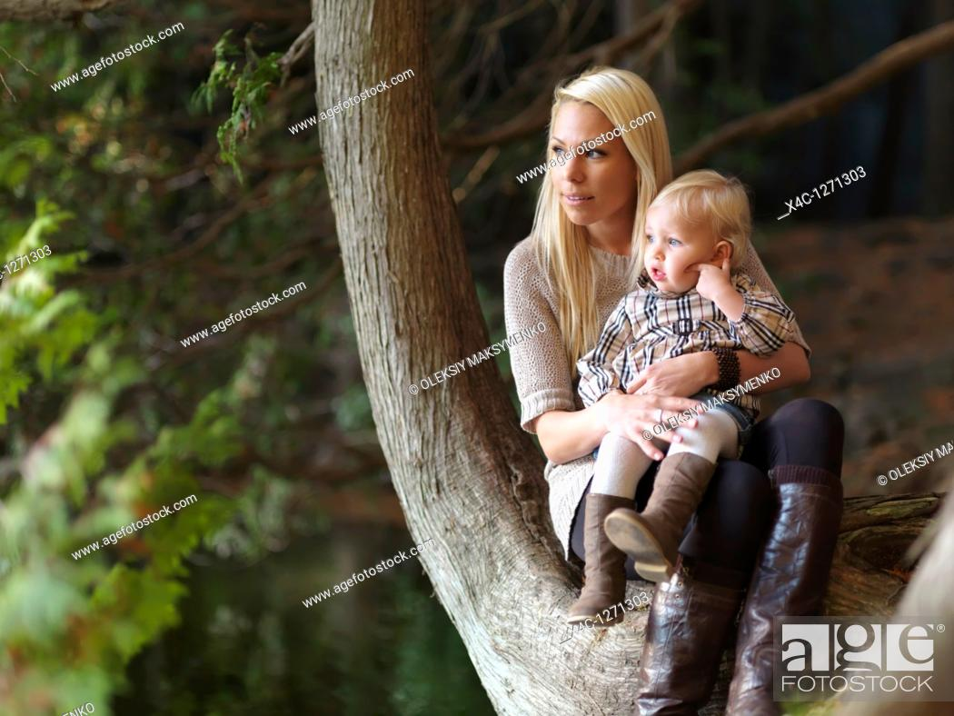 Stock Photo: Young mother with a two year old daughter sitting at a lake in the nature  Ontario, Canada.