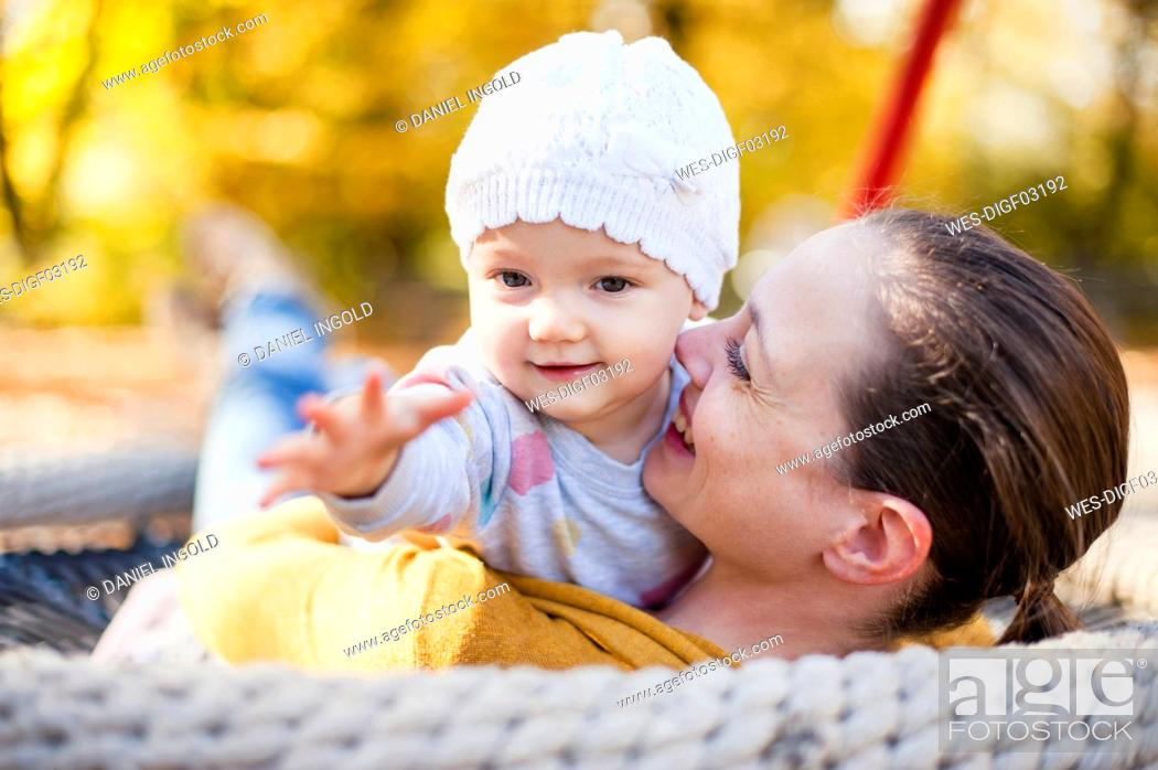 Stock Photo: Portrait of baby girl relaxing with her mother on a swing in autumn.