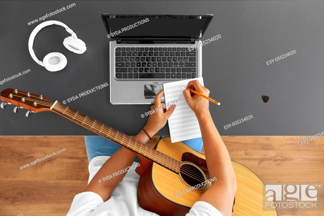 Imagen: man with guitar writing to music book at table.