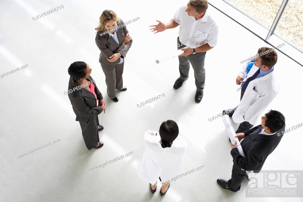 Stock Photo: Businesspeople standing having a meeting.
