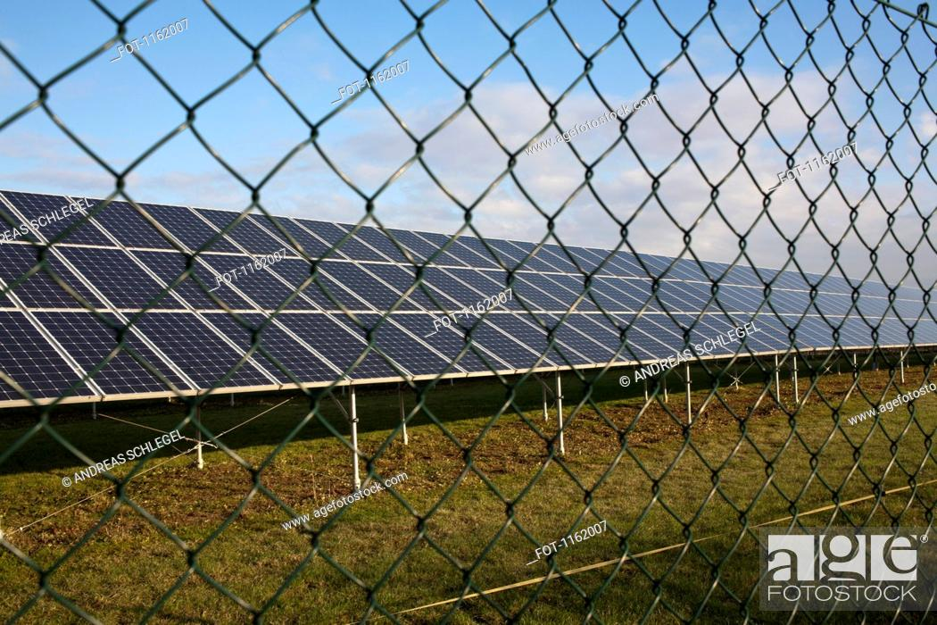 Stock Photo: Solar panels behind chain link fence.