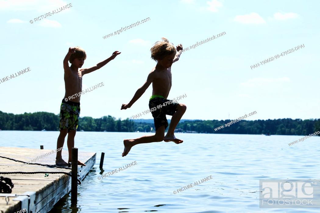 Stock Photo: 02 June 2019, Brandenburg, Berlin: Two children play at the jetty at a lake in Brandenburg. Photo: Annette Riedl/dpa. - Berlin/Brandenburg/Germany.