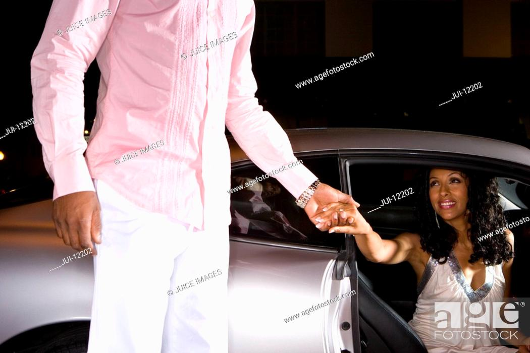 Stock Photo: Man helping woman from car at night, low angle view.