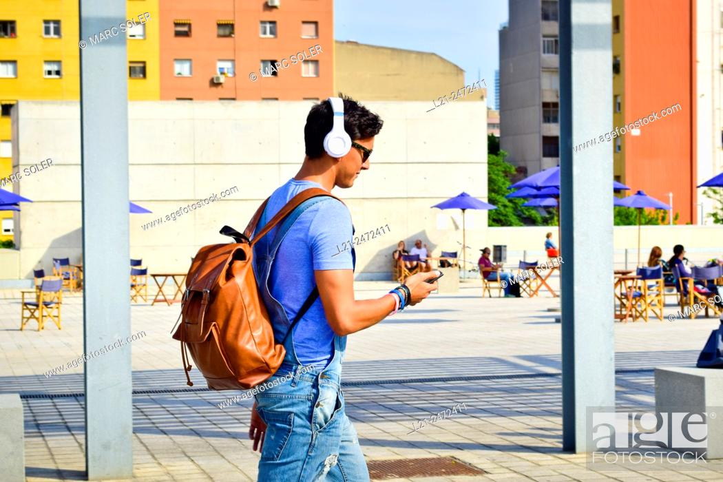 Stock Photo: Young fashionable man with headphones, sunglasses and backpack walking while watching his smart-phone. Plaça de les Glòries Catalanes, Barcelona, Catalonia.