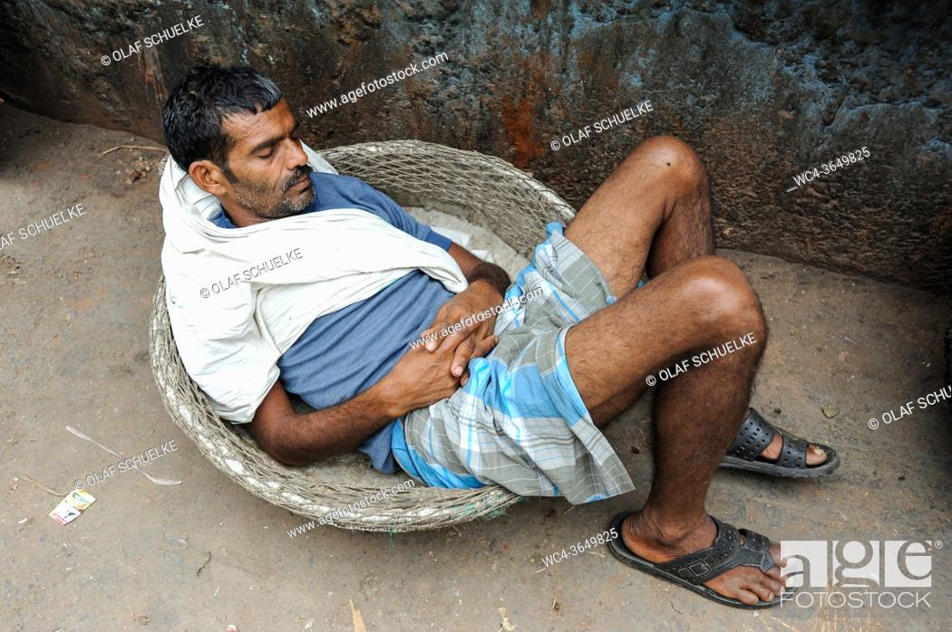 Stock Photo: Kolkata (Calcutta), West Bengal, India, Asia - A street scene in the East Indian metropolis shows a day labourer who rests on the side of a road waiting to.