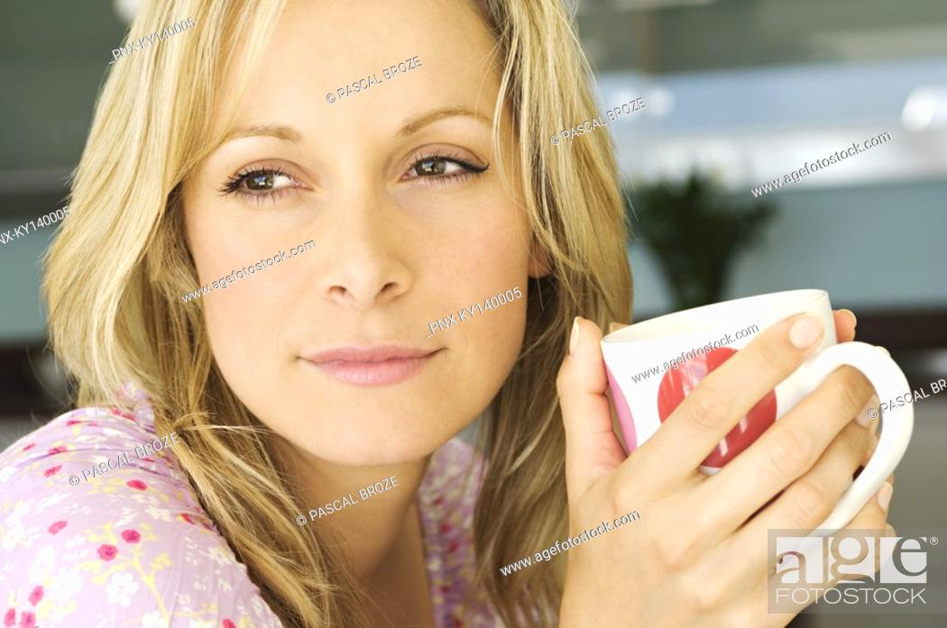 Stock Photo: Portrait of a young thinking woman, holding mug.
