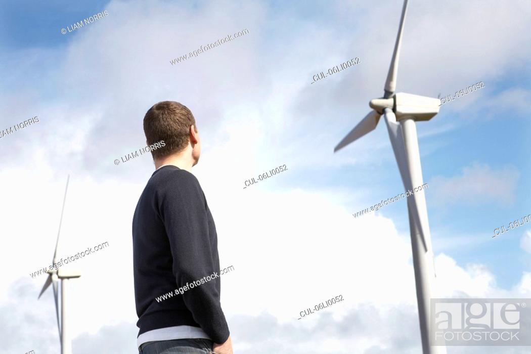 Stock Photo: Man looking at wind turbines.