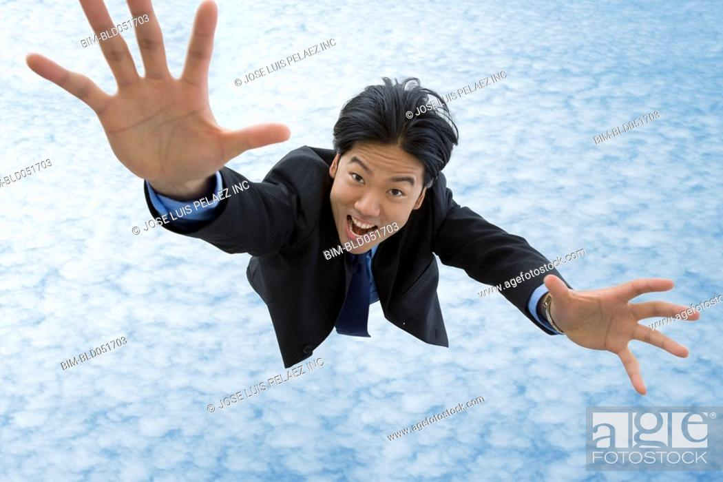 Stock Photo: Asian businessman falling in sky.