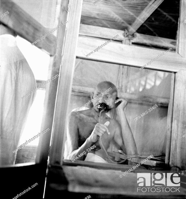 Stock Photo: Mahatma Gandhi telephoning from the office hut at Sevagram Ashram, Vardha, Maharashtra, India, 1938 - MODEL RELEASE NOT AVAILABLE.